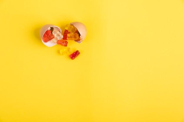 Casca de ovo dividida e aberta sobre fundo amarelo e gomas sobre ela