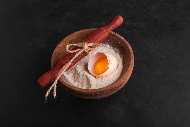 Casca de ovo e gema dentro de uma xícara de farinha na superfície preta.