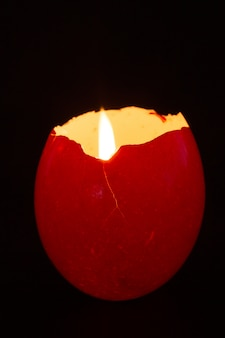 Casca de ovo vermelha utilizada como suporte de vela