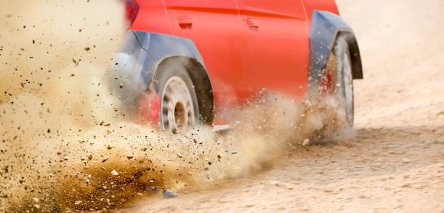 Cascalho espirrando de deriva de carro de corrida de rali na pista
