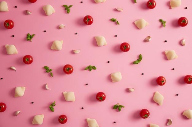 Cascas clássicas de massa de trigo duro com tomates frescos, manjericão verde, alho, pimenta para cozinhar a saborosa cozinha italiana. fundo de comida. massa crua com vegetais de ervas. vista superior, configuração plana