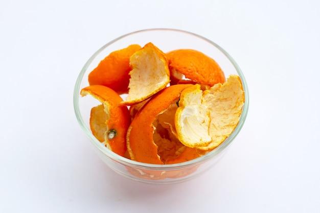 Cascas de laranja em uma tigela de vidro na superfície branca