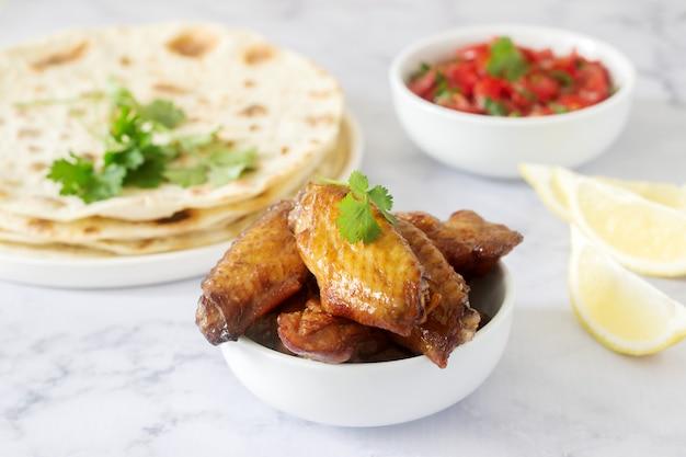 Caseira deliciosa comida de tortilhas, salsa e asas fritas.