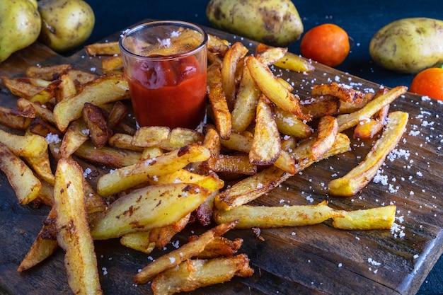 Caseiro batata frita com ketchup na terra traseira de madeira