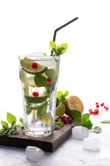Caseiro mojito cocktail com limão, limão, folhas de hortelã, com gelo e groselha. conceito de bebida de verão.