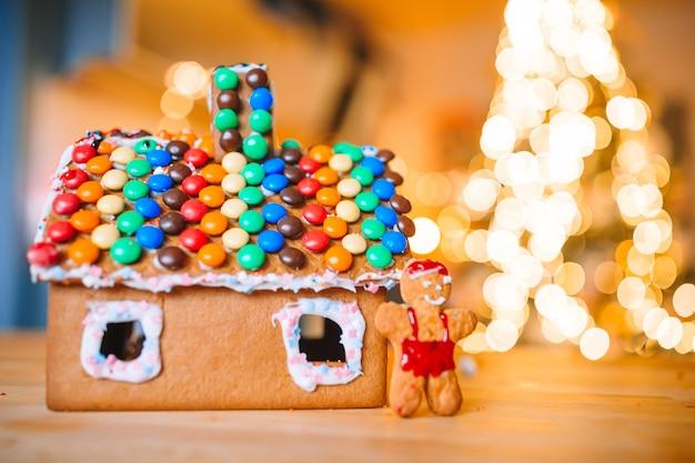 Caseiro natal gingerbread house em uma mesa. luzes da árvore de natal ao fundo