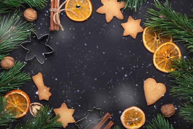 Caseiros biscoitos frescos ramos de abeto fatias secas de laranja conceito de natal de cortadores de biscoito