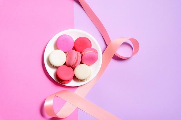 Caseiros macaroons coloridos ou macaron em fundo branco rosa e roxo de plateon