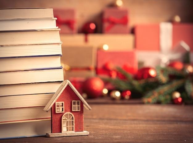 Casinha de brinquedo com livros e presentes de natal na mesa de madeira