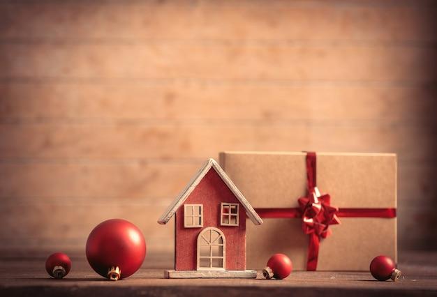 Casinha de brinquedo e presente de natal na mesa de madeira