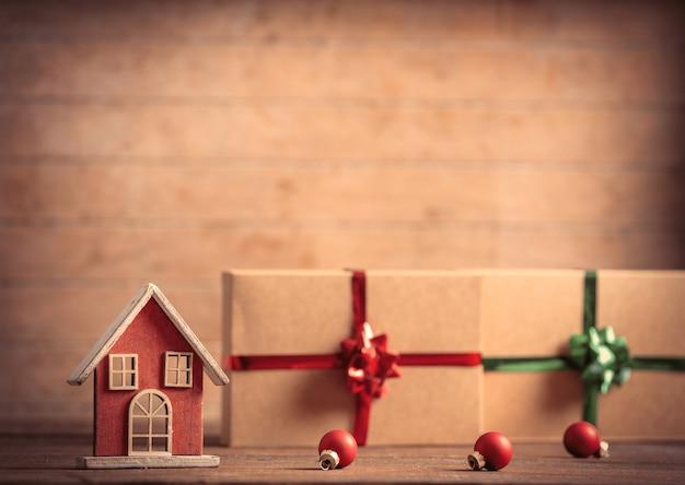 Casinha de brinquedo e presentes de natal na mesa de madeira