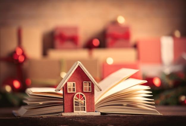 Casinha e livro aberto com gfits de natal na mesa de madeira