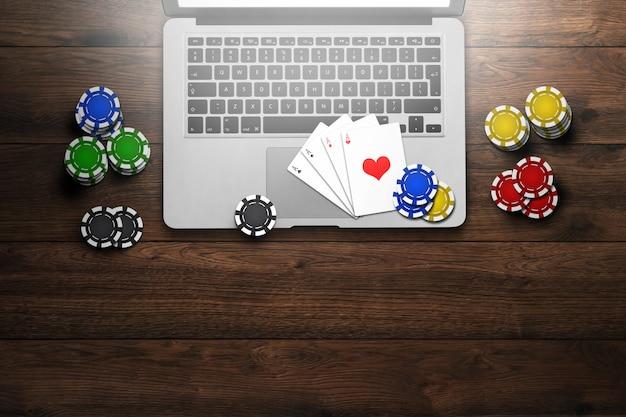 Casino online, computador portátil, cartões com fichas na madeira