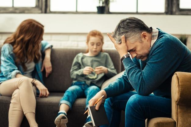 Caso difícil. homem triste e triste sentado na poltrona enquanto se cansa de seus pacientes Foto Premium