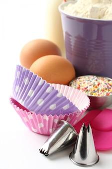 Casos de cupcake e ingredientes sobre branco com copyspace