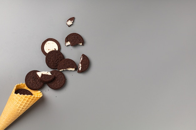 Casquinha de sorvete com biscoitos de chocolate com recheio em fundo cinza