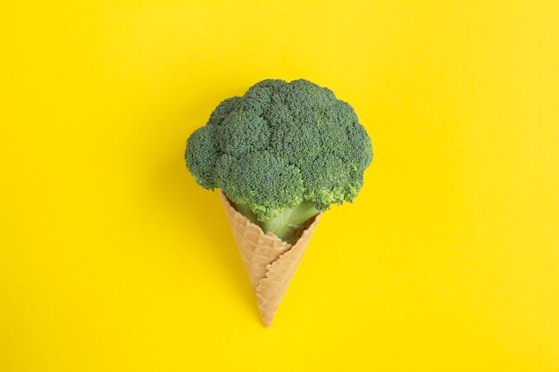 Casquinha de sorvete com brócolis no fundo amarelo