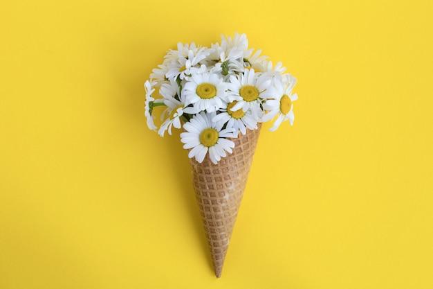Casquinha de sorvete com camomilas no centro do fundo amarelo. vista superior. copie o espaço. conceito de flores de primavera ou verão.