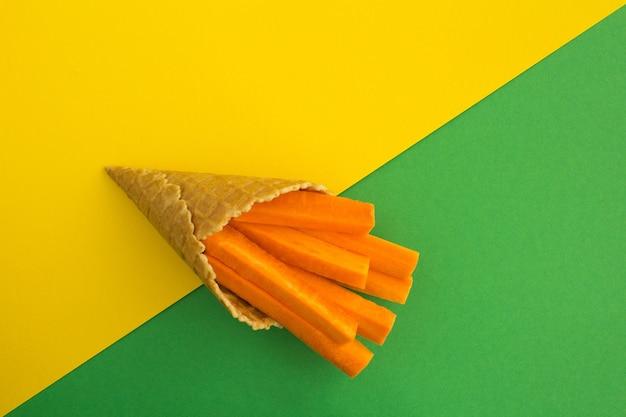 Casquinha de sorvete com cenouras fatiadas. vista superior. copie o espaço.