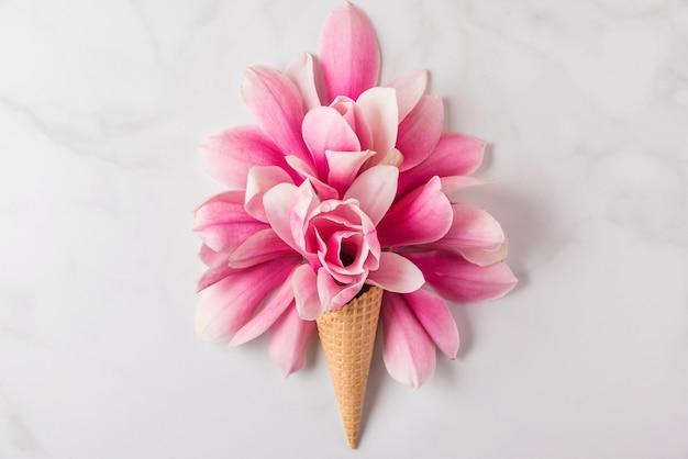 Casquinha de sorvete com composição de flores de magnólia rosa primavera. conceito de primavera mínima. configuração plana