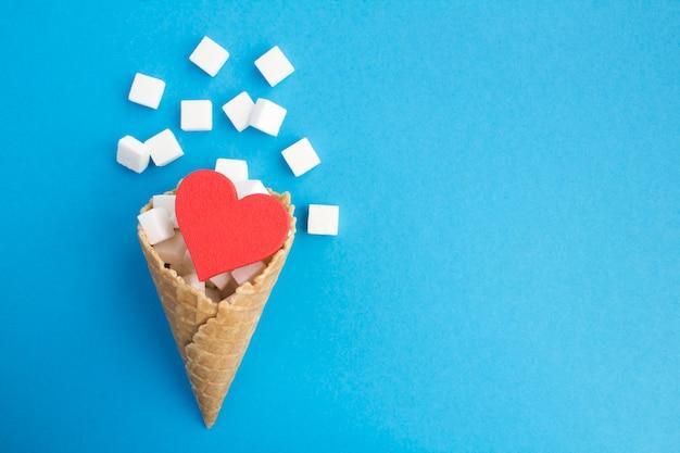 Casquinha de sorvete com coração vermelho e açúcar branco no fundo azul