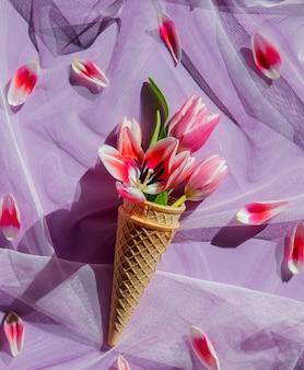 Casquinha de sorvete com flor de tulipa e pétalas em volta da superfície de tule roxo