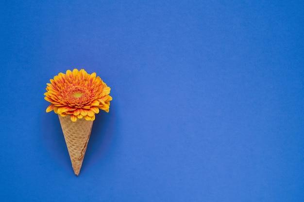 Casquinha de sorvete com flor gerbera amarela sobre fundo azul. copie o espaço, vista superior.