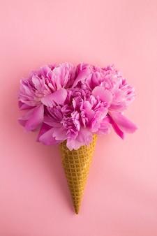 Casquinha de sorvete com peônias rosa no centro do fundo rosa