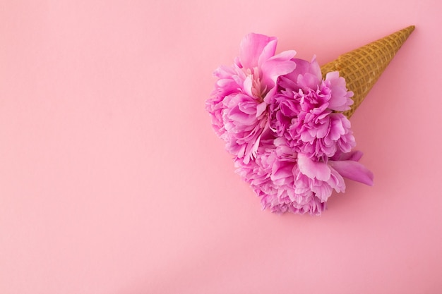 Casquinha de sorvete com peônias rosa. vista superior. copie o espaço. conceito de flores de primavera.