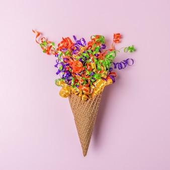Casquinha de sorvete com serpentinas coloridas de festa no fundo rosa.
