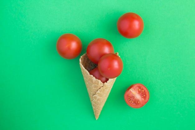 Casquinha de sorvete com tomate vermelho sobre fundo verde