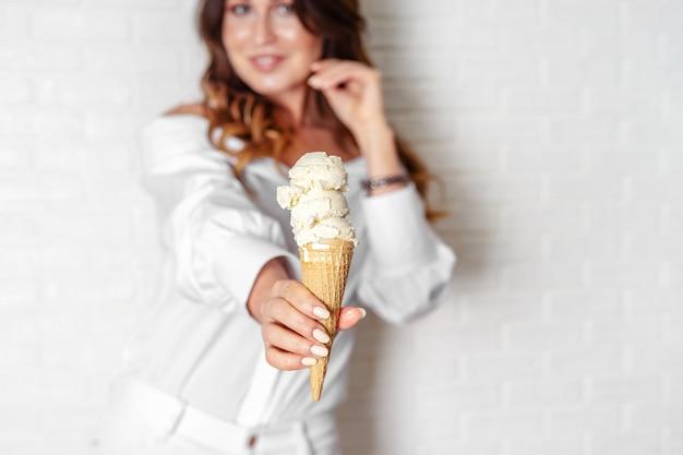 Casquinha de sorvete de baunilha em closeup de mão de mulher