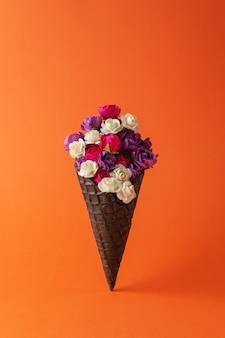 Casquinha de sorvete preto com flores coloridas em fundo brilhante.