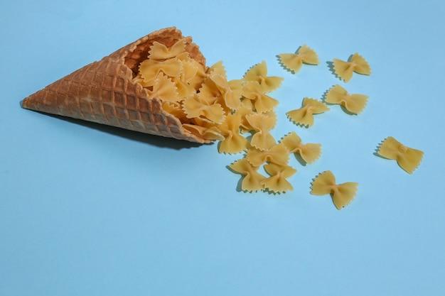 Casquinha de waffle de sorvete com laços de massa em fundo azul pastel