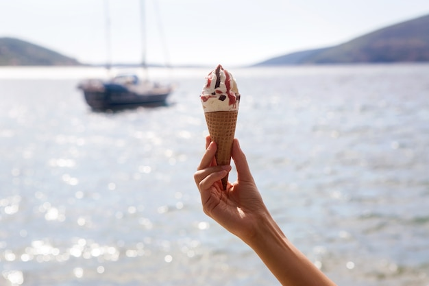 Casquinhas de sorvete com chocolate e geléia em uma mão feminina em um fundo de mar e iates