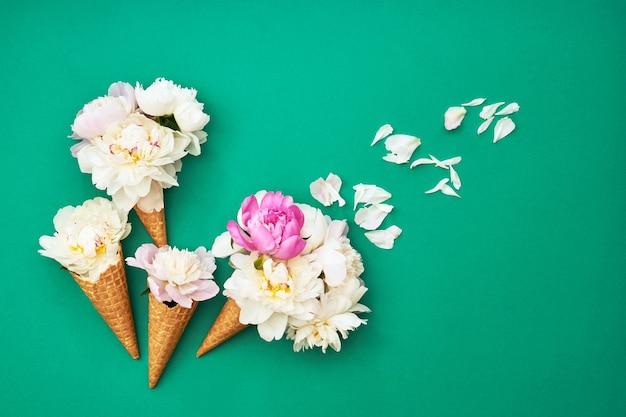 Casquinhas de sorvete com flores de peônia branca na mesa verde. conceito de verão. copiar espaço, vista superior