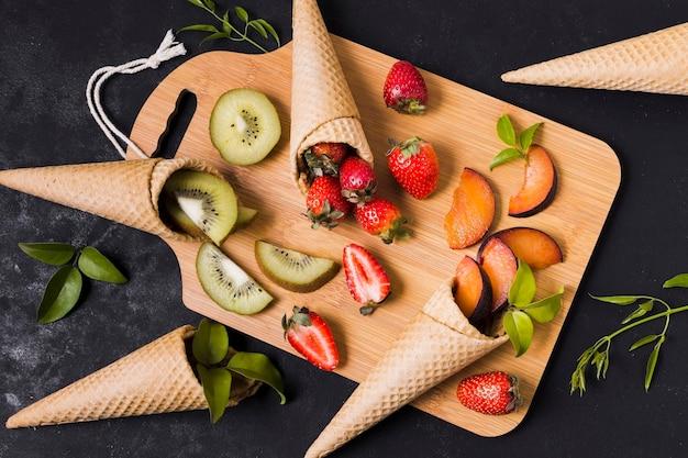 Casquinhas de sorvete com frutas frescas na mesa de madeira