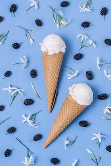 Casquinhas de sorvete de baunilha brancas cercadas por flores e frutas