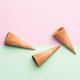 Casquinhas de sorvete vazio marrom saboroso na superfície multicolorida