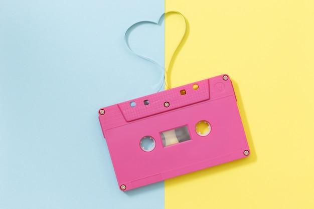 Cassete áudio com fita magnética na forma do coração - imagem do estilo do efeito do vintage. conceito mínimo.