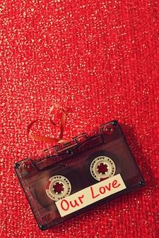 Cassete áudio retrô com fita em forma de coração em superfície texturizada vermelha