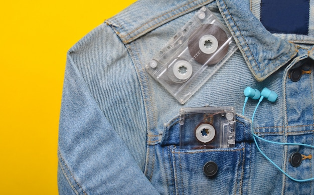Cassete de áudio e fones de ouvido no bolso de uma jaqueta jeans hipster em um fundo amarelo. entretenimento anos 80. com música na vida.