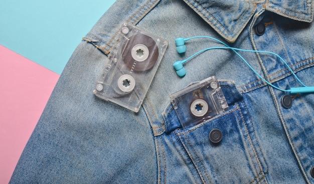 Cassete de áudio e fones de ouvido no bolso de uma jaqueta jeans hipster em um fundo de cor creme rosa azul. entretenimento anos 80. com música na vida.
