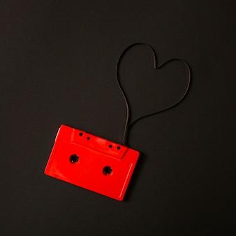 Cassete de áudio vermelho com fita magnética em forma de coração em fundo preto