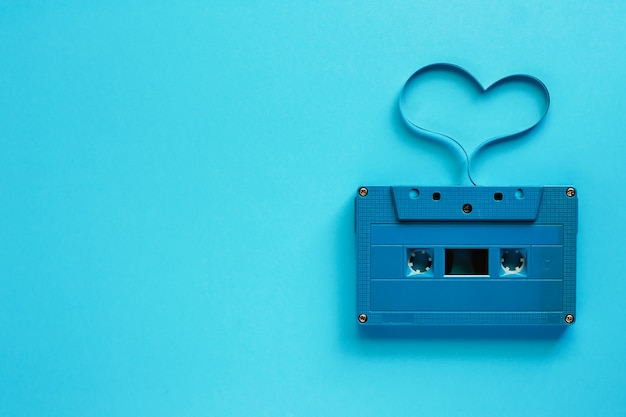 Cassete de banda magnética retro com forma do coração no fundo azul para o conceito da música e do amor