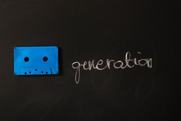 Cassete de fita azul e palavra de geração em fundo preto