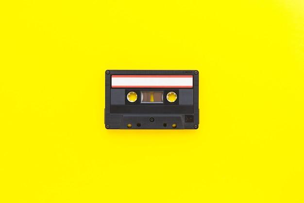 Cassete de fita de áudio retrô dos anos 80 e 90, isolada em fundo amarelo. conceito de tecnologia antigo. camada plana, vista superior com espaço de cópia.