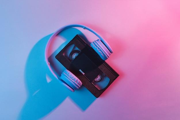 Cassete de vídeo com fones de ouvido. onda retrô, luz de neon, ultravioleta. vista superior, minimalismo