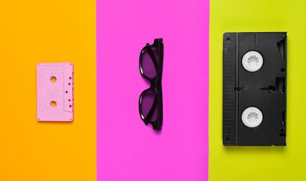 Cassete de vídeo, óculos de sol, cassete de áudio em um papel multicolorido.