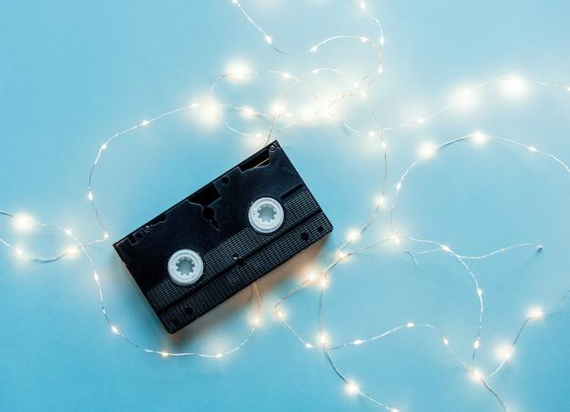 Cassete vhs dos anos 80 com luzes de fada em fundo azul